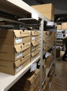 高価なシープスキンブーツは、入庫時に一足ずつ丁寧に専用ケースに入れ、品番別にラックに整然と並びます。